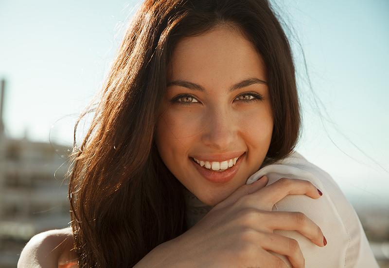Brunette in a white blouse enjoying the sunny day
