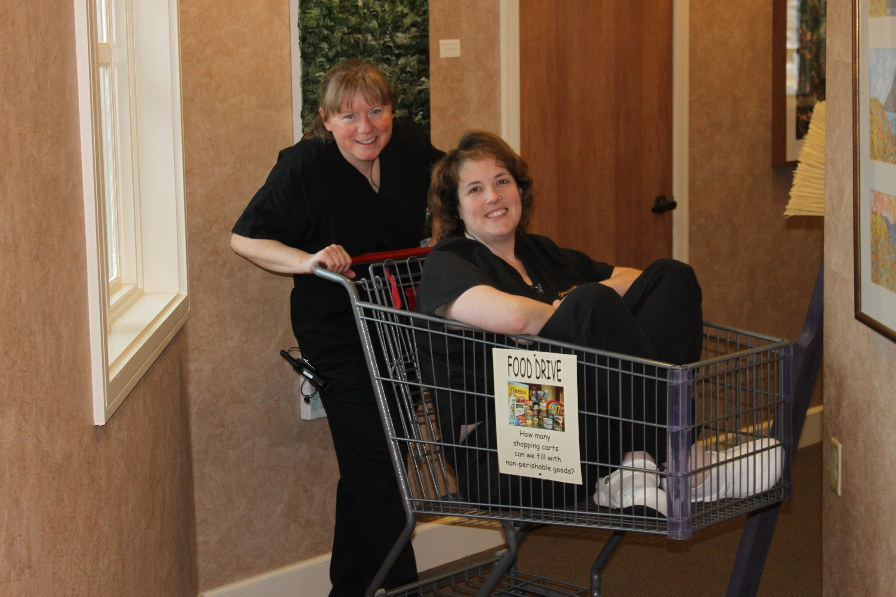 Kathryn pushing Janet in a shopping cart for a food drive for the local Food Pantry