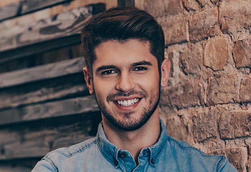 Man in a denim button down shirt against a brick and wood wall