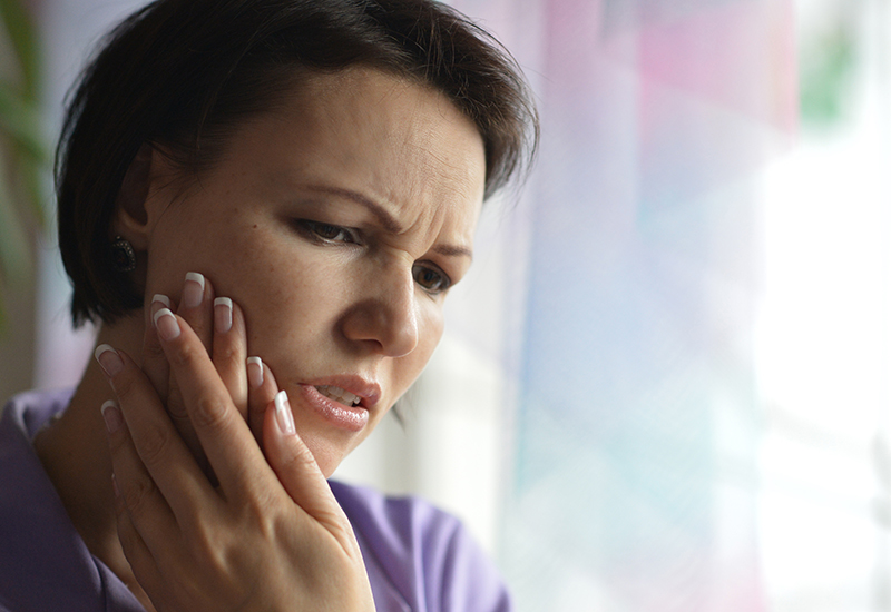 Brunette woman with her hands cradling her painful right jaw