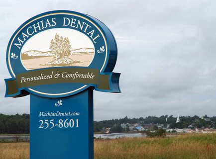 Machias Dental signage with field, river, and town in the background